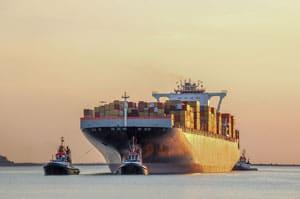 Tug boats guiding a cargo ship to port.