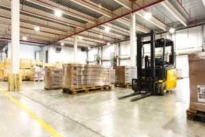 Organized pallets and forklift in a warehouse.