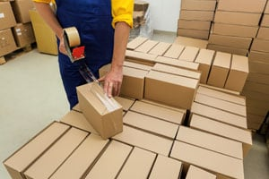 Logistics services - Warehouse worker taping a box on a pallet